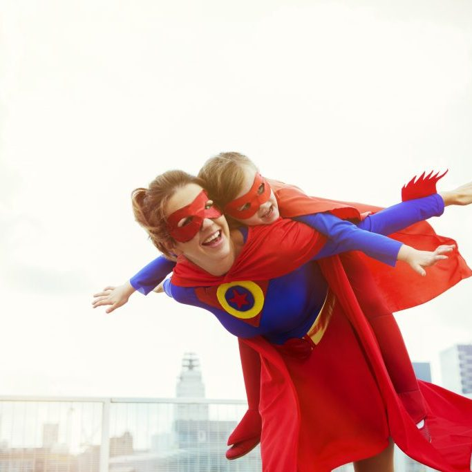 Superhero mother and daughter playing on city rooftop